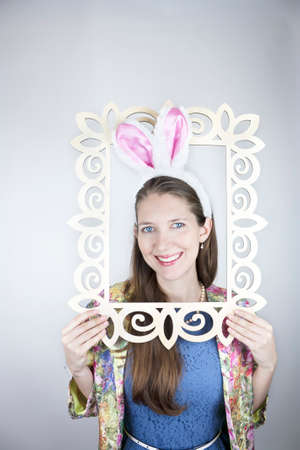 Young woman wearing rabbit ears and coming out of picture frame photo