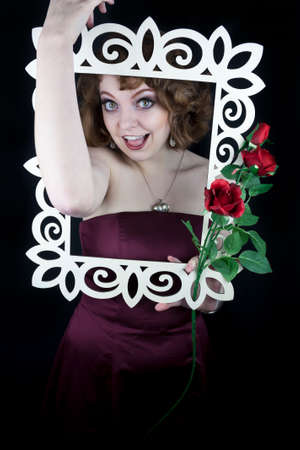 Beautiful woman holding white wooden frame with red roses with her arms  photo