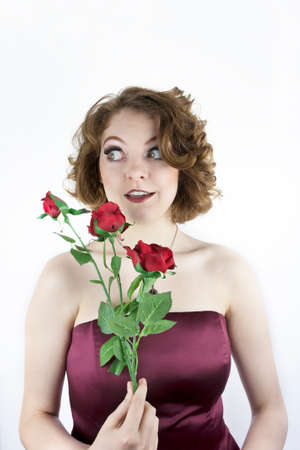 strapless: Beautiful young woman wearing strapless, satin dress holding red roses