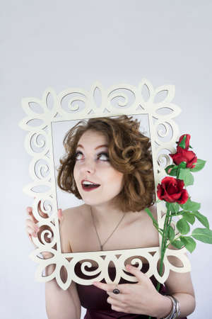 Beautiful young woman wearing strapless burgundy dress posing with white picture frame and red roses photo