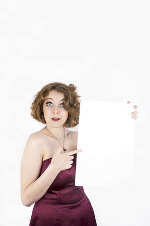 Beautiful woman wearing strapless burgundy dress and holding blank sign for copy space  photo