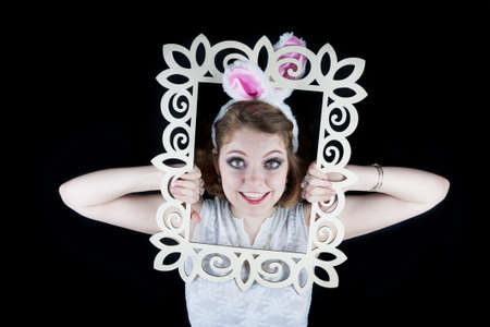 Young woman posing with rabbit ears and white frame on black background