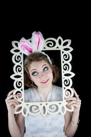 Young woman posing with rabbit ears and white frame on black background  photo