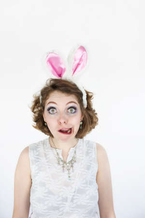 Beautiful young woman wearing Easter rabbit ears making funny face