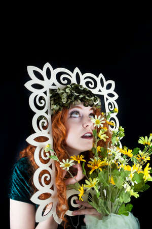 Pretty woman with long, curly red hair posing with picture frame and yellow flowers photo