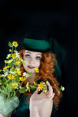 Beautiful young woman wearing top hat with green tulle wrapped abound the top photo