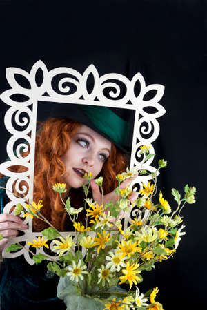 Beautiful young woman with long, curly red hair wearing a top hat posing with yellow flowers and a picture frame photo