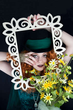 Beautiful young woman with long, red hair wearing a top hat posing with picture frame photo