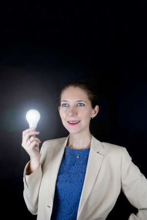 Pretty business woman wearing blue dress and yellow jacket holding a light bulb photo