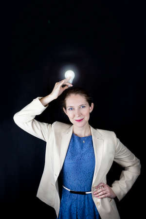 Pretty business woman wearing blue dress and yellow jacket holding a light bulb over her head photo