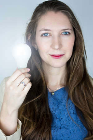 Pretty business woman wearing blue top and yellow jacket holding lit light bulb photo