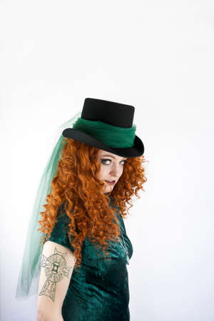velvet dress: Beautiful young woman with long, red curly hair wearing a top hat showing her tattoo of a Celtic cross