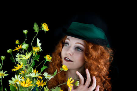 Beautiful young woman wearing top hat with green tulle wrapped abound the top