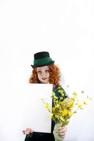 velvet dress: Beautiful young Irish girl with long, curly, red hair dressed in velvet green dress and top hat with green tulle holding yellow flowers and blank sign