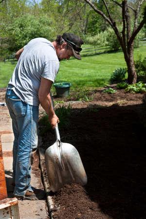 Man with shovel mulching a garden Zdjęcie Seryjne