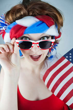 Young woman dressed in red, white and blue holding American flag and sunglasses Stock Photo