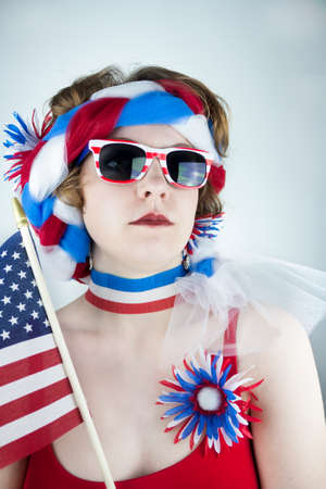 Young woman dressed in red, white and blue holding American flag and looking serious Stock Photo