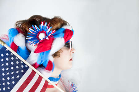 Young woman dressed in red, white and blue with American flag over her shoulder
