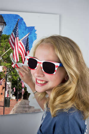 Pretty young blond girl painting flags and wearing 4th of July sunglasses