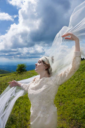 Young bride on mountain top with veil blowing in the veil