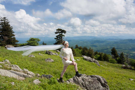 Young bride in black boots on a mountain top Stock Photo