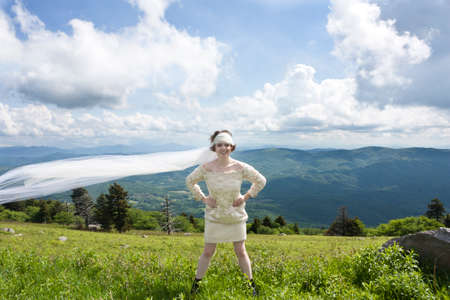 Young bride with long veil blowing in the wind on mountain top Stock Photo