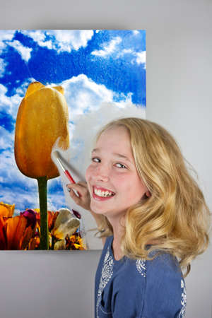 Cute blond girl wearing blue painting yellow tulip in a tulip field