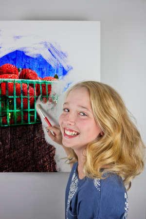 Cute blond girl wearing blue painting strawberries