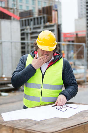 worker man: Construction worker with yellow hardhat and safety jacket checking blueprint Stock Photo