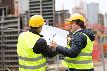 new construction: Construction worker with yellow hardhat and safety jacket checking blueprint with an architect Stock Photo