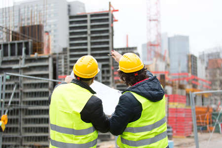 Back turned construction workers with yellow hardhat and safety jacket checking blueprint office