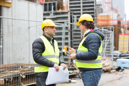 construction site: Workers with safety jacket and yellow hardhat talking reviewing plans at construction site