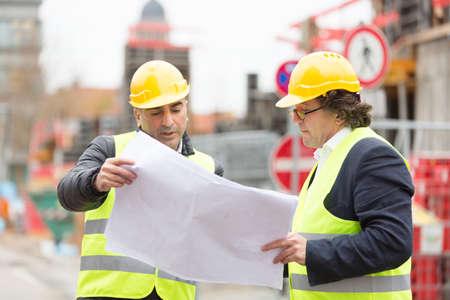 Deux ingénieurs avec des plans au chantier de construction