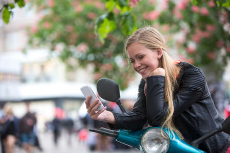 Cute young woman on a scooter laughing looking at the phone Stock Photo