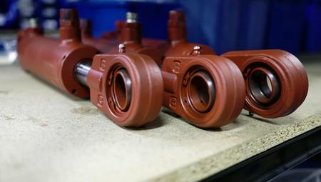 Tres cilindros hidráulicos marrones se encuentran en una fila sobre una superficie de madera