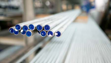 Many metal pipes with blue tips are kept in stock.