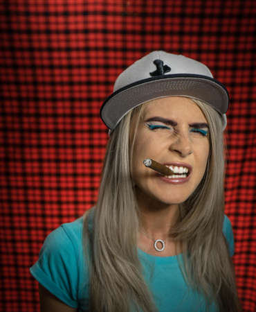 A sexy smoking beautiful hipster woman in a white cap and a turquoise T-shirt with a cigar. Evil face, grin. Teenage style, Grunge