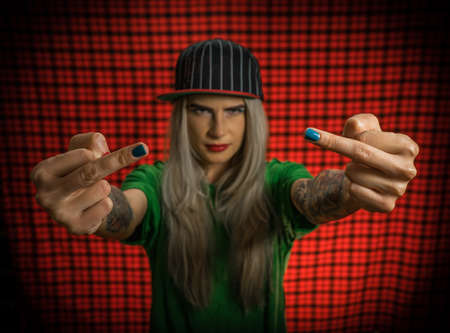 A young hipster girl shows the middle finger with an expression of an evil smile. Street fashion, portrait in a cap