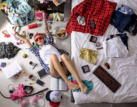 after studying blonde student, lying on the floor in headphones and sunglasses, stretches, listening to music The image of a modern student, education. Accessories of a modern young girl Archivio Fotografico