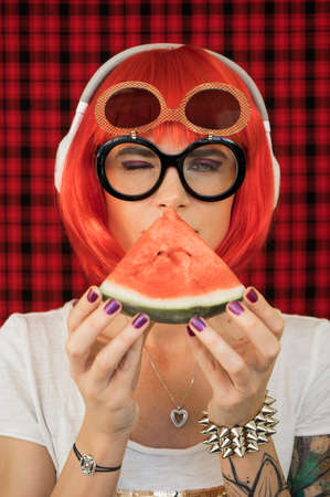 A fashionable woman in a red wig and glasses, listening to music in white headphones and holding a piece of ripe watermelon. Summer image of a modern teenage girl