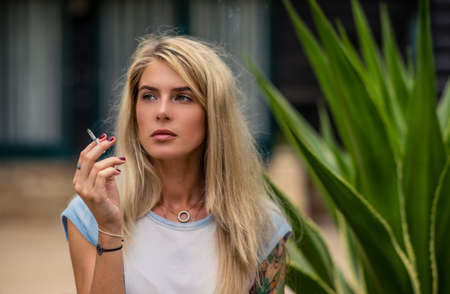 Beautiful blonde girl smokes a cigarette. Womens hands with a tattoo. Urban fashion