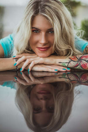 Closeup portrait of. Beautiful girl put her head in her arms with tattoos. expectation. Imagens