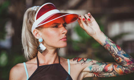 The girl in the red visor looking into the distance. Arms tattooed. Modern beach-ready look. Stock Photo