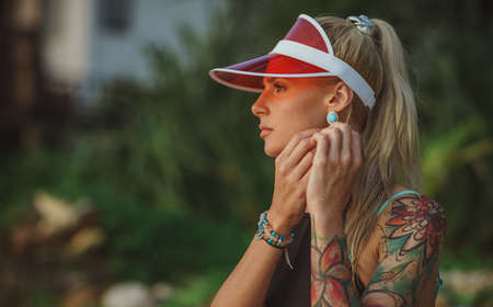 Portrait of a beautiful girl in a red visor closeup. Corrects large earrings. Holiday in Thailand Stock Photo