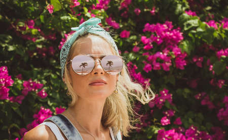 Close-up portrait of a young beautiful girl in glasses with reflection of tropical palms. Summer rest. Modern tourist