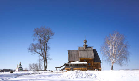 Old wooden church in a field between two trees. Travel to Russia