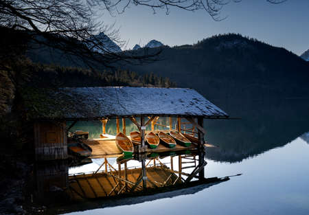 Boat station on the mountain lake Fussen Germany. Sunlight on boats