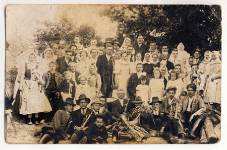 Group photoghaph taken at wedding in the Slovak village (Central Europe). In the foreground is a brass band. Date: 1920. Without image restoration. Stock Photo - 24920605