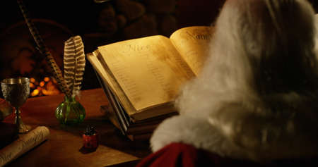 View over Santa's shoulder of naughty/nice list 写真素材