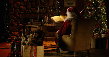 Santa Claus works at his desk, surrounded by Christmas decorations Stock Photo
